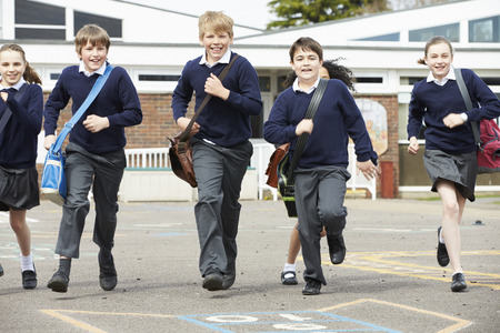 Grupo de alumnos de la escuela primaria que se ejecutan en patio