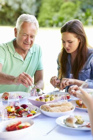 adult offspring: Multi Generation Family Enjoying Outdoor Meal Together Stock Photo