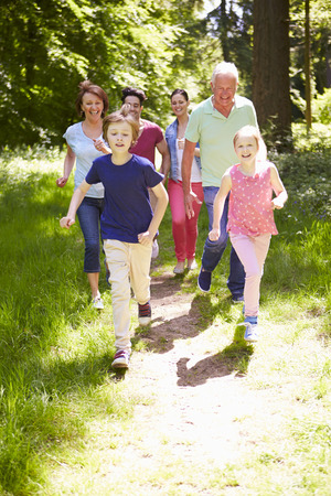 active girl: Multi Generation Family Running Through Summer Countryside Stock Photo