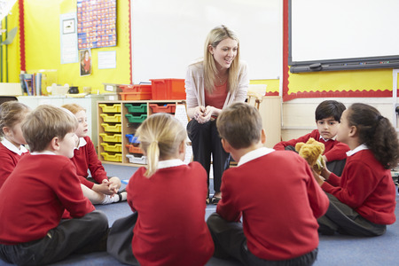 children learning: Elementary School Pupils Telling Story To Teacher