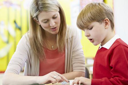 niños estudiando: Profesor de ayuda a la pupila masculina con la lectura en el escritorio