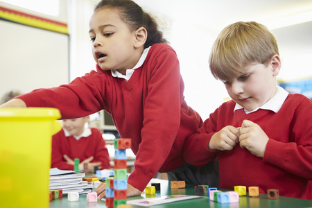 elementary: Pupils Working With Coloured Blocks In Maths Lesson Stock Photo