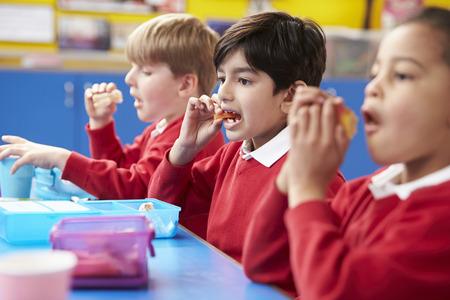 lunch: Los escolares sentado en la mesa Comer Almuerzo en lonchera