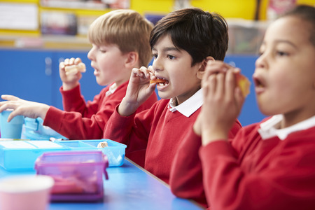 school year: Schoolchildren Sitting At Table Eating Packed Lunch