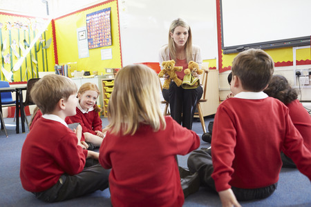 toy story: Teacher Telling Story To Elementary School Pupils Stock Photo