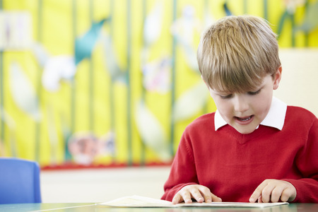school table: Male Pupil Reading Book At Table Stock Photo