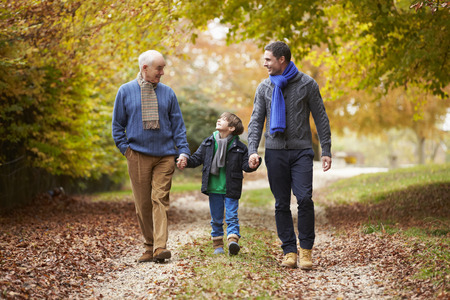 father and son holding hands: Male Multl Generation Family Walking Along Autumn Path
