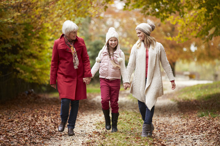 grandmother mother daughter: Female Multl Generation Family Walking Along Autumn Path Stock Photo