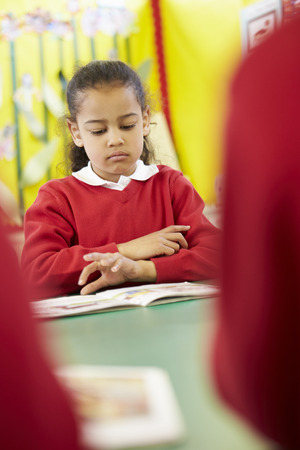 the pupil: Female Pupil Reading Book At Table Stock Photo