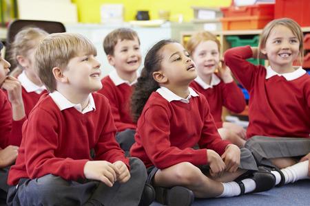 ni�os sentados: Los alumnos sentado en la lona que escucha el profesor