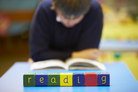 spelt: Word Reading Spelt In Wooden Blocks With Pupil Behind Stock Photo