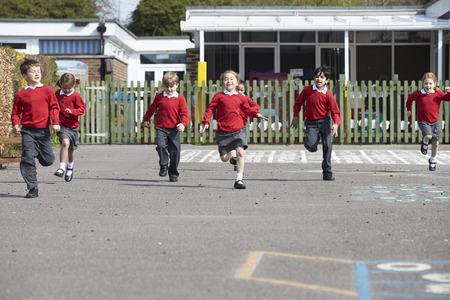 ni�os sanos: Los alumnos de la escuela primaria que se ejecutan en patio