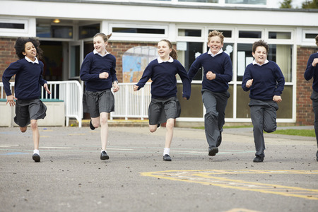 uniforms: Group Of Elementary School Pupils Running In Playground