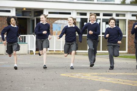 niños jugando en la escuela: Grupo de alumnos de la escuela primaria que se ejecutan en patio