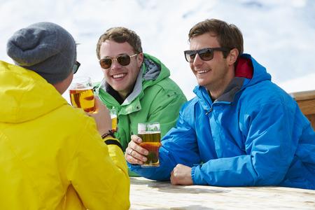 hombre con sombrero: Grupo de j�venes disfrutan de la bebida en bares a la estaci�n de esqu� Foto de archivo