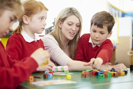 school year: Pupils And Teacher Working With Coloured Blocks Stock Photo