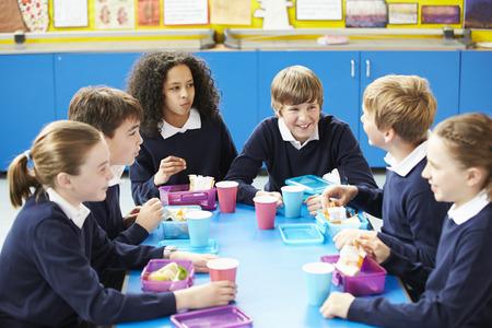 uniformes: Los escolares sentado en la mesa Comer Almuerzo en lonchera