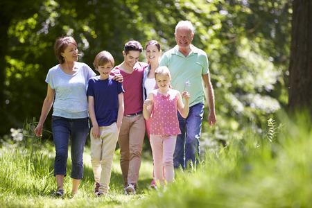 Multi Generation Familie die door Summer Countryside Stockfoto