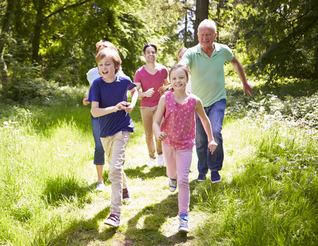 11 year old girl: Multi Generation Family Running Through Summer Countryside Stock Photo