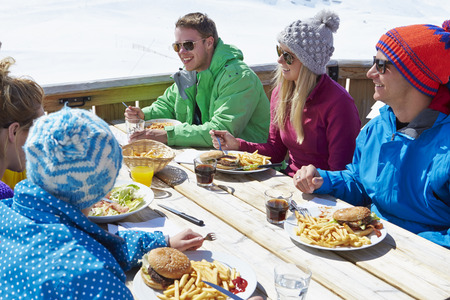 Baráti társaság örvendő Étkezési Cafe A Ski Resort Stock fotó
