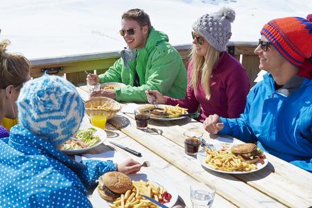 Gruppe Freunde, die Mahlzeit genießen In Cafe Am Skigebiet