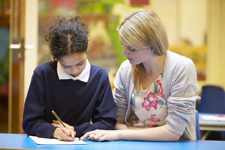 uniformes: Profesor Con Mujer Alumno de lectura en el escritorio en sala de clase Foto de archivo