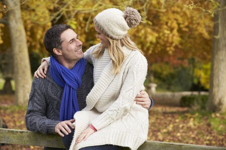 couple outdoor: Romantic Couple Sitting On Fence In Autumn Woodland
