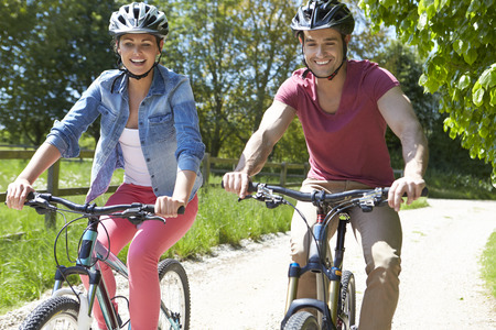 cycle ride: Young Couple On Cycle Ride In Countryside Stock Photo