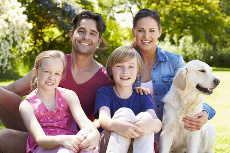 thirties portrait: Portrait Of Family With Dog  Relaxing In Summer Garden Stock Photo