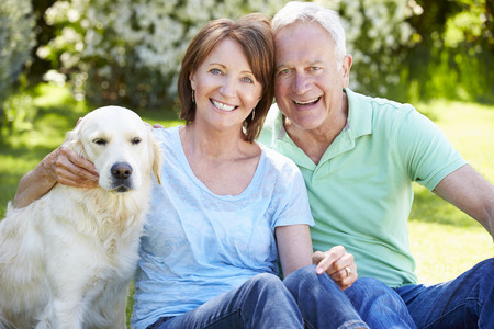 Portrait Of Senior Couple Sitting In Garden With Dog