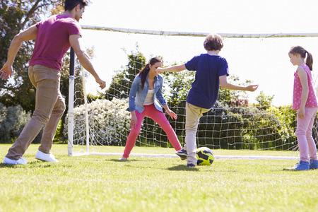 jugando futbol: Familia que juega a fútbol Juntos Foto de archivo