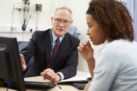 doctor computer: Consultant Meeting With Patient In Office Stock Photo
