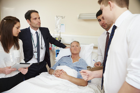 Medical Staff On Rounds Standing By Male Patients Bed