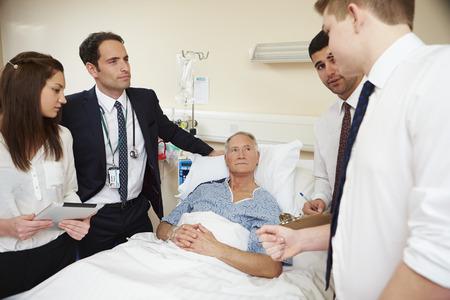 Personal médico en Rondas de pie junto cama Hombre del paciente