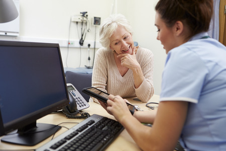test results: Nurse Showing Patient Test Results On Digital Tablet Stock Photo