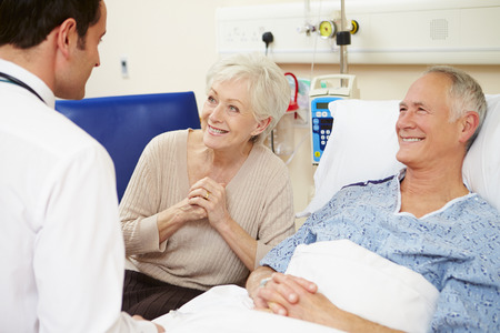 Doctor Talking To Senior Couple By Hospital Bed