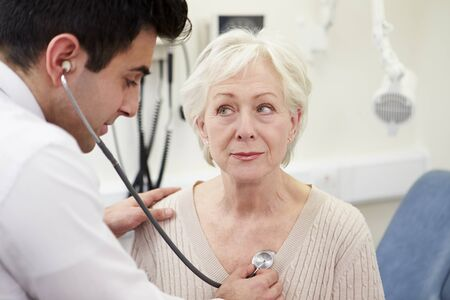 patient in hospital: Doctor Examining Senior Female Patient In Hospital Stock Photo
