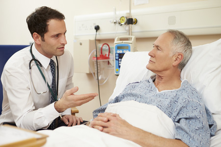 Doctor Sitting By Male Patient's Bed In Hospital Banque d'images