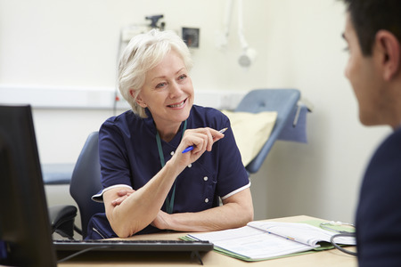 one to one meeting: Female Nurse Meeting With Male Patient Stock Photo