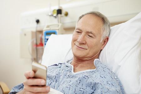 hospitales: Paciente masculino senior usando el teléfono móvil en cama de hospital