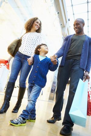 niños de compras: Niño en viaje al centro comercial con los padres