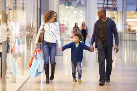 Kind Op reis naar winkelcentrum met ouders Stockfoto