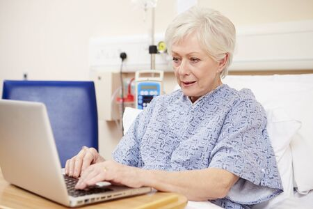 hospital patient: Senior Female Patient Using Laptop In Hospital Bed