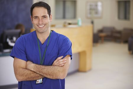 one person: Portrait Of Male Nurse In Hospital Reception Stock Photo