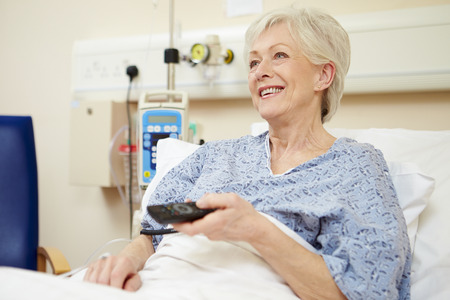 woman watching tv: Senior Female Patient Watching TV In Hospital Bed Stock Photo