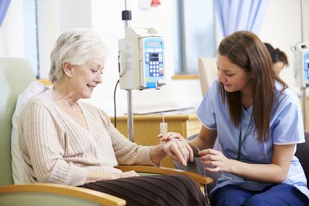 Ältere Frau, die eine Chemotherapie mit Krankenschwester