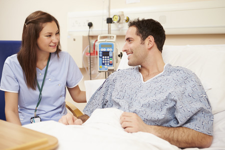 Nurse Sitting By Male Patients Bed In Hospital Stock Photo