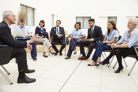 staff team: Members Of Medical Staff In Meeting Together Stock Photo