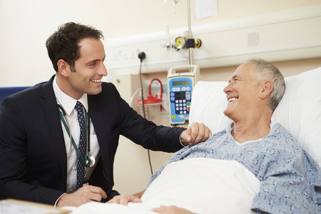 reassurance: Doctor Sitting By Male Patients Bed In Hospital