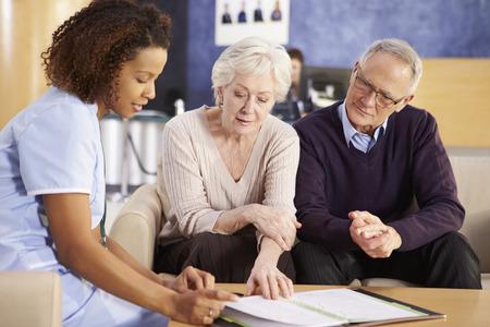 Senior paar ontmoeting met verpleegkundige in het ziekenhuis Stockfoto